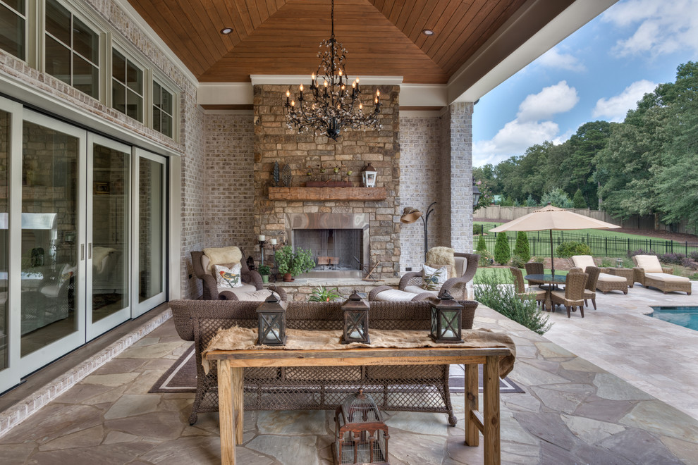 Large mountain style backyard stone patio photo in Other with a roof extension and a fireplace