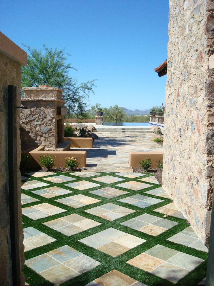 Example of a tuscan patio design in Phoenix with no cover