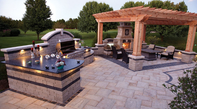 Inspiration for a large contemporary backyard concrete paver patio kitchen remodel in Other with a pergola