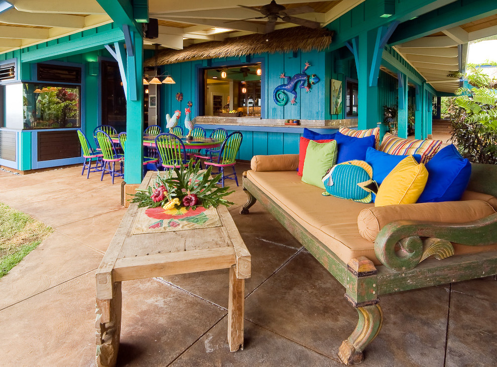 Example of a large island style backyard tile patio kitchen design in Hawaii with a roof extension