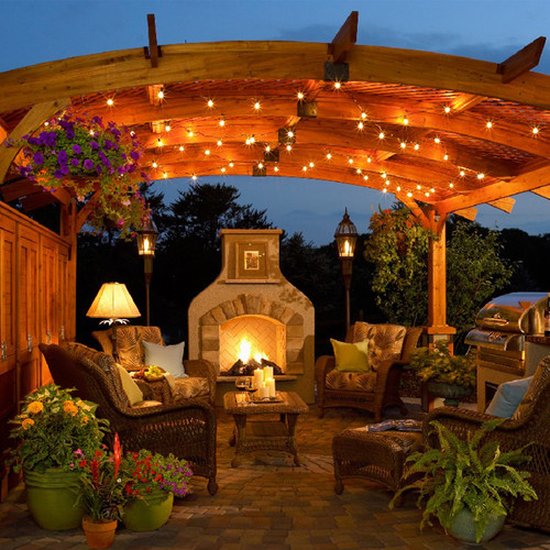 add some punch to your pergola with a sheltering arch then string it with lights for a veil of dappled illumination outdoor string lights like these can - Outdoor Patio Looks