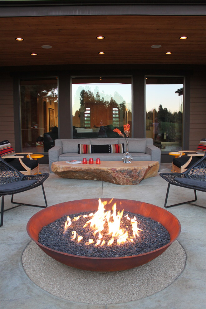 Example of a large trendy backyard concrete patio design in Other with a fire pit and a roof extension