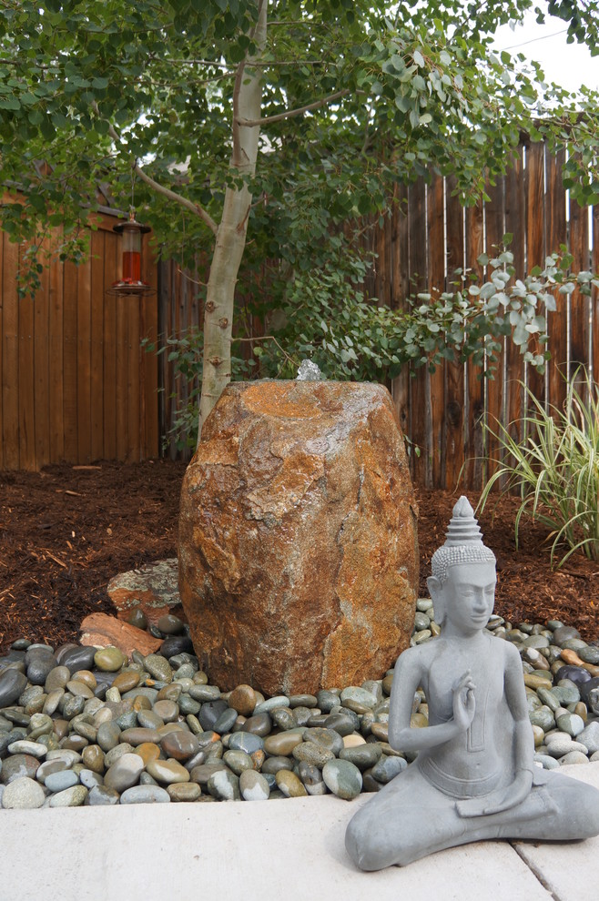 Inspiration for a small courtyard concrete patio fountain remodel in Denver with no cover