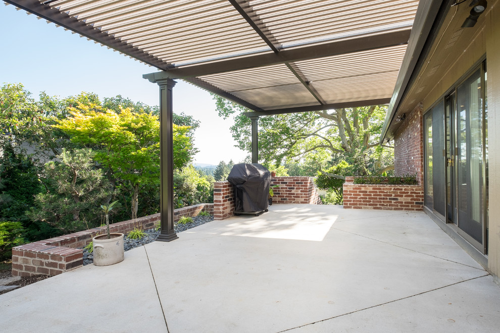Patio - large transitional side yard concrete patio idea in Portland with an awning