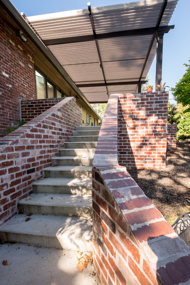 Inspiration for a large transitional side yard concrete patio remodel in Portland with an awning
