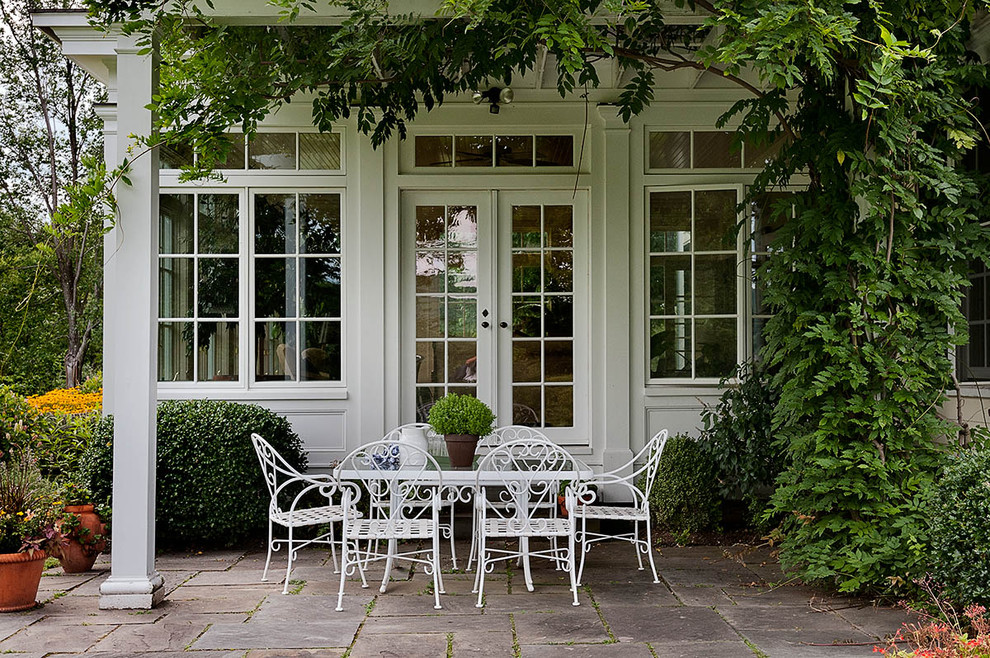 French country patio photo in New York with a pergola