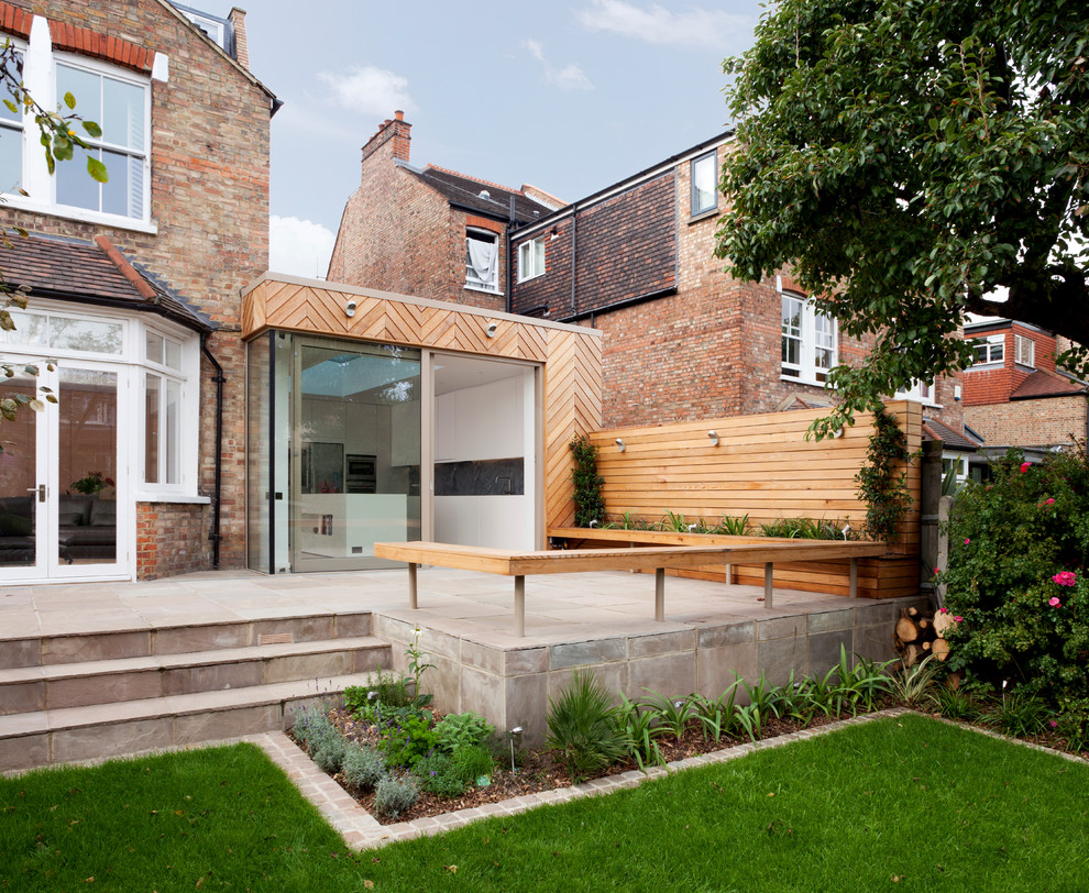Large contemporary back patio in London with natural stone paving and no cover.