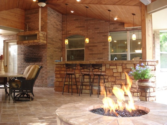 Houston covered patio with rustic fire pit bar area for Cost of outdoor living space