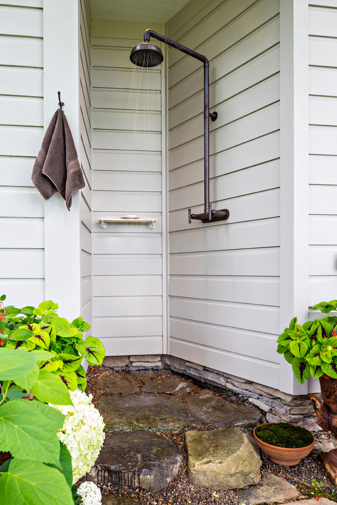 Inspiration for a farmhouse backyard stone outdoor patio shower remodel in New York with a roof extension