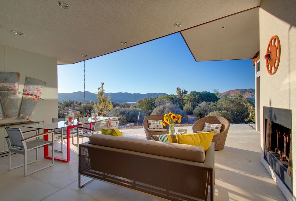 1960s concrete patio photo in Los Angeles with a roof extension and a fireplace