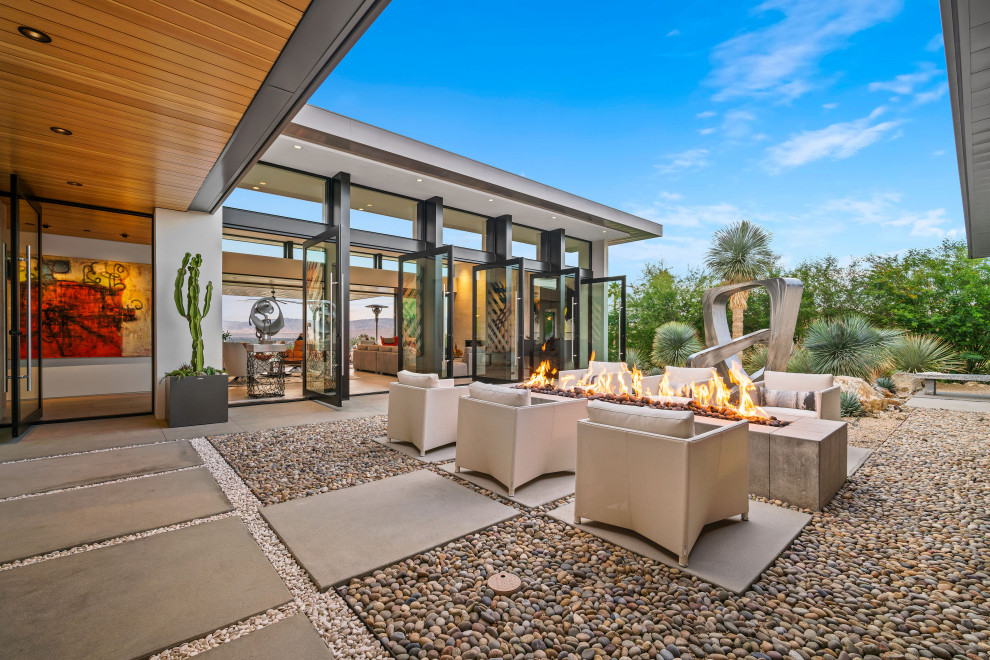 Example of a trendy courtyard patio design in Los Angeles with a fire pit and no cover