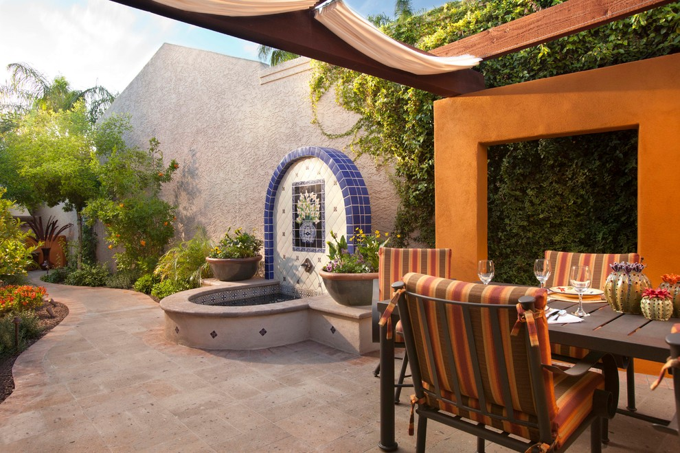 Example of a tuscan patio fountain design in Phoenix with a pergola