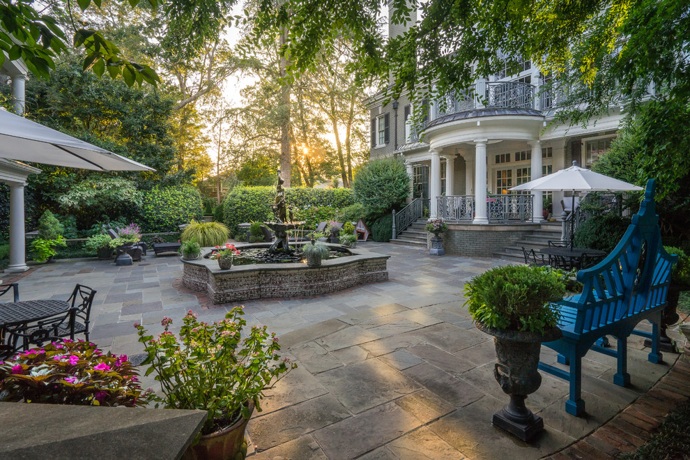 Inspiration for a large timeless backyard stone patio fountain remodel in Other with a roof extension