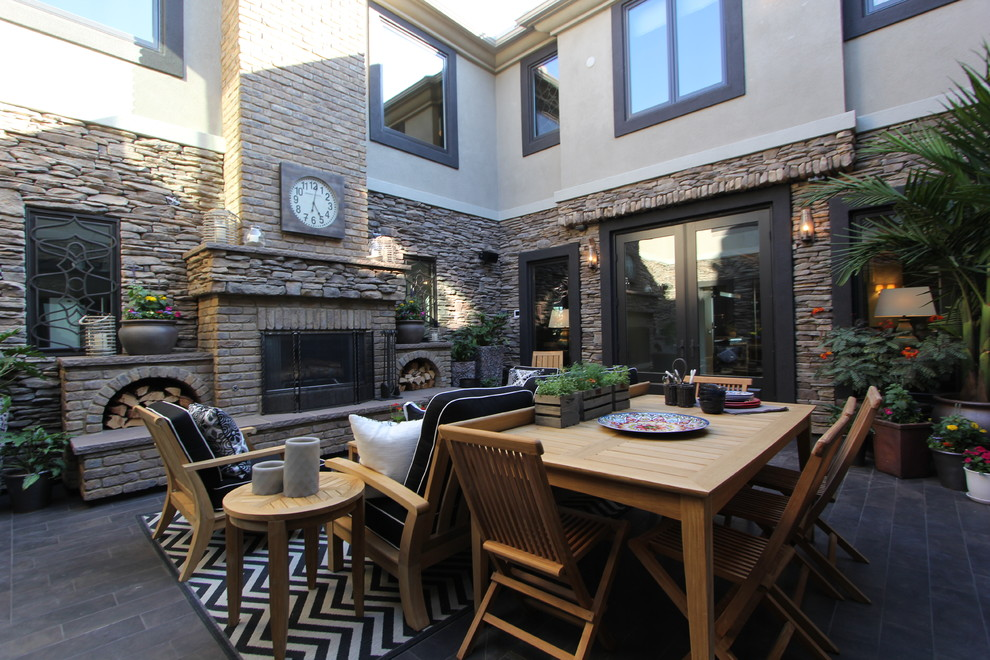 Elegant courtyard patio photo in San Diego with a fire pit