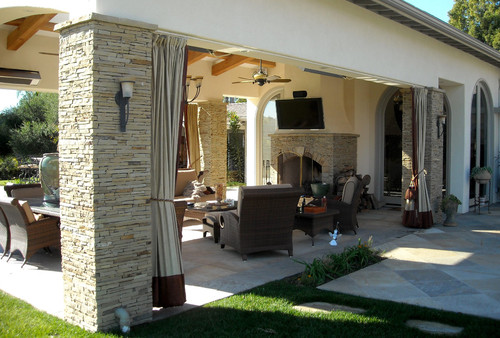 outdoor entertaining can get cozy with curtains to block the wind