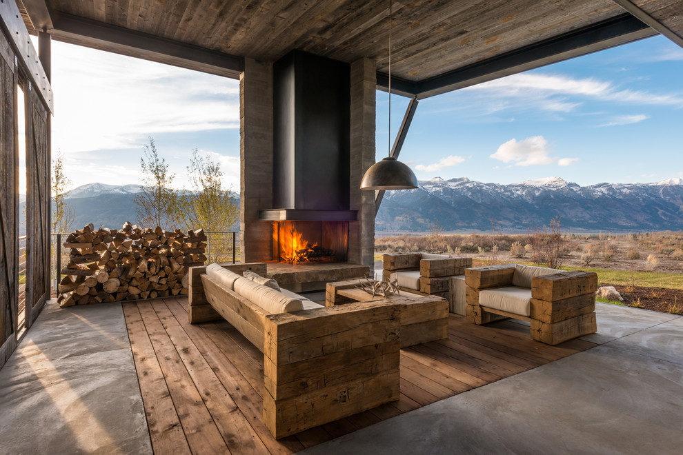 Example of a huge mountain style backyard concrete patio design in Other with a fire pit and a roof extension