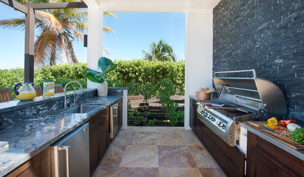 Example of an island style patio kitchen design in Other with a pergola
