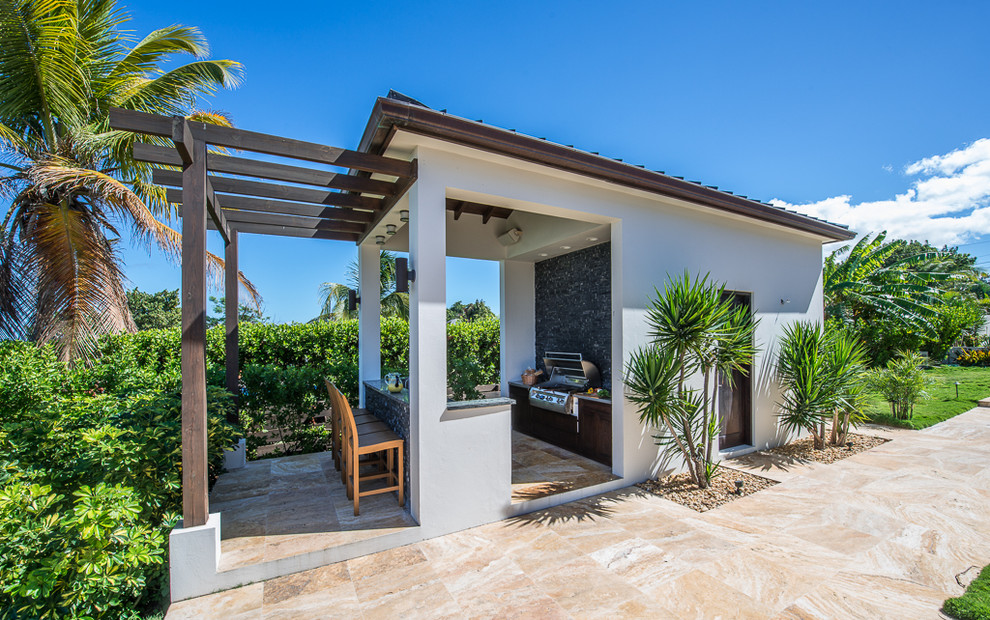 Example of an island style patio design in Other with a pergola