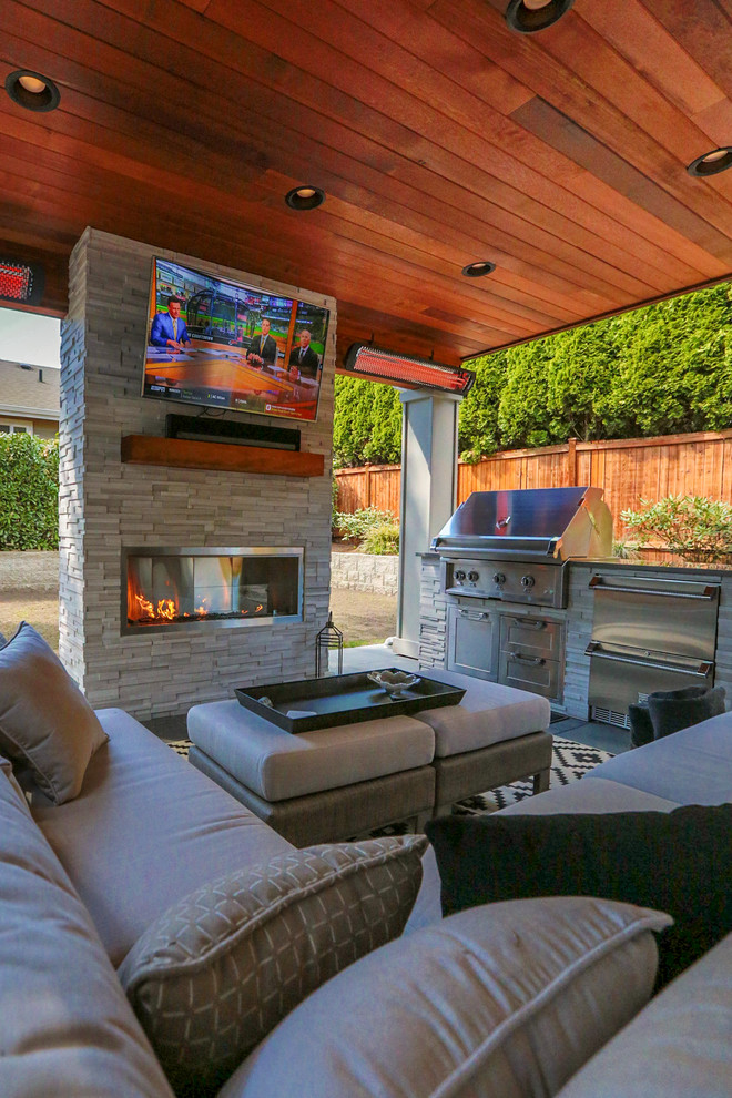 Inspiration for a mid-sized modern backyard concrete paver patio kitchen remodel in Seattle with a roof extension