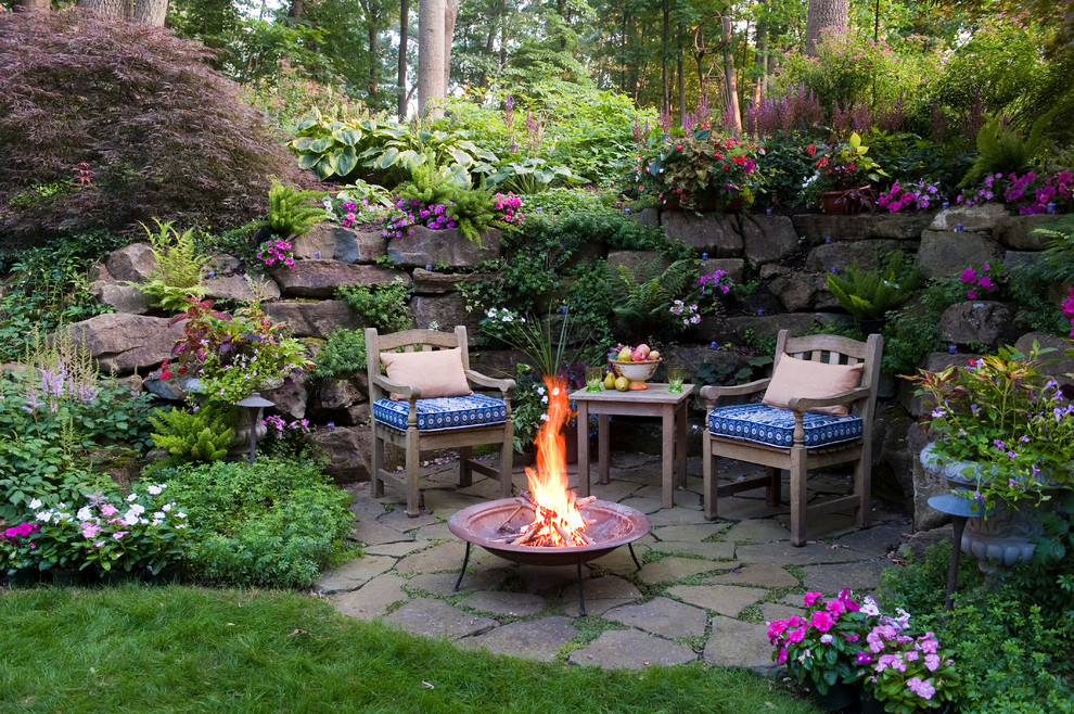 Example of a classic backyard stone patio design in Philadelphia with a fire pit and no cover