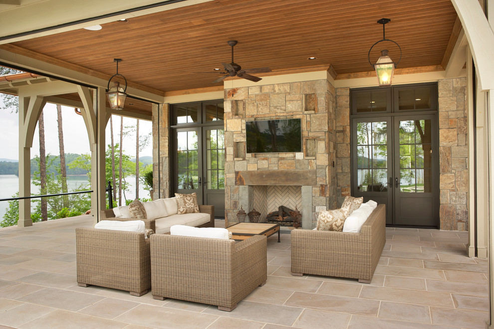 Large elegant backyard stone patio photo in Other with a roof extension