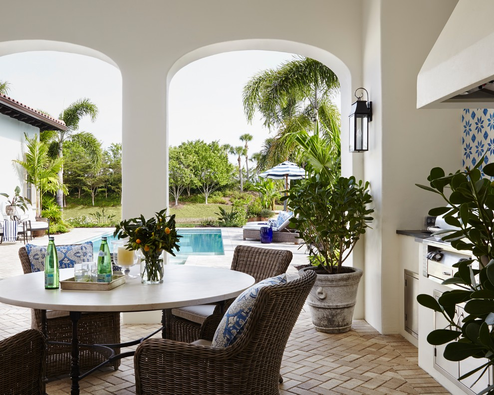 Large island style backyard brick patio kitchen photo in Miami with a roof extension