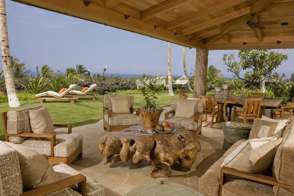 Inspiration for a tropical stone patio remodel in Hawaii with a roof extension