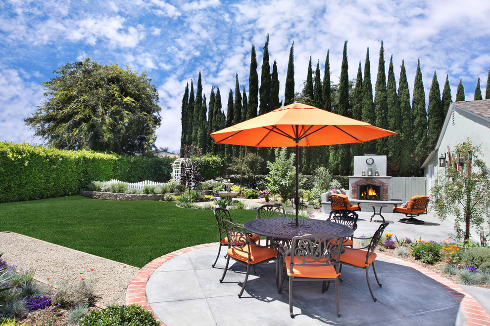 Inspiration for a large timeless backyard concrete patio remodel in Orange County with a fire pit and no cover