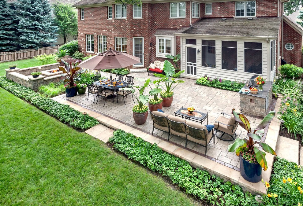 Example of a large classic backyard brick patio design in Chicago with a fire pit and no cover