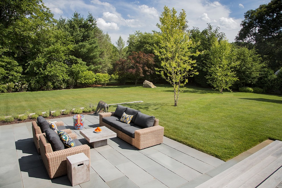 Example of a large minimalist backyard stone patio design in Boston with no cover