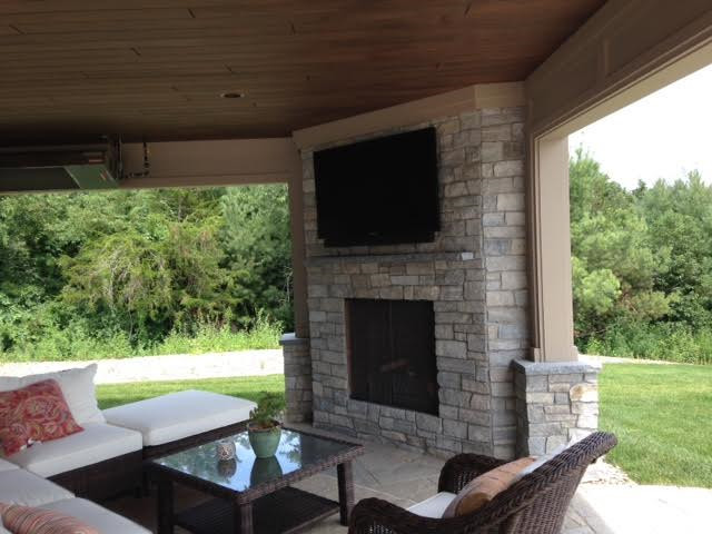 Inspiration for a rustic backyard stone patio remodel in New York with a fire pit and a roof extension