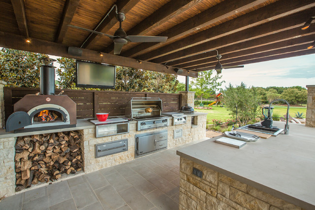 large elegant backyard stone patio kitchen photo in dallas with a roof extension - Patio Kitchen
