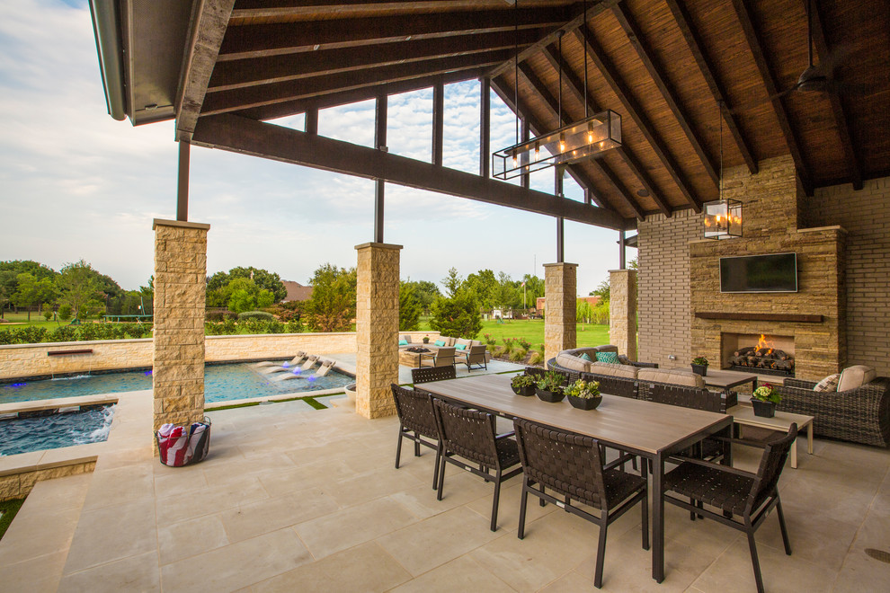 Inspiration for a large timeless backyard stone patio remodel in Dallas with a roof extension and a fireplace