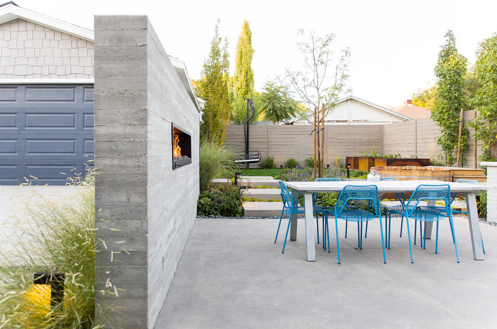 Example of a trendy side yard concrete patio design in Salt Lake City with a fireplace and no cover