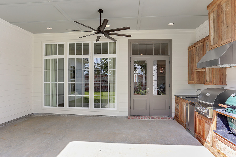 Example of a mid-sized classic backyard concrete patio kitchen design in New Orleans with a roof extension