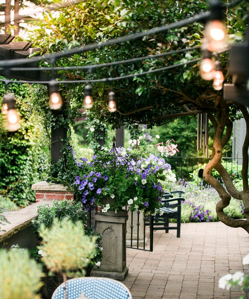 Inspiration for a mid-sized timeless backyard brick patio container garden remodel in Seattle with a pergola