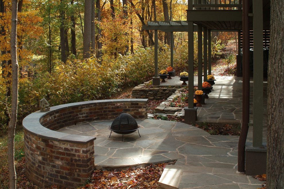 Example of a mountain style stone patio design in DC Metro with a fire pit and a pergola