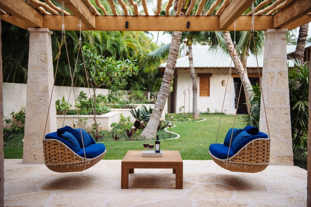 Mid-sized island style backyard stone patio container garden photo in Hawaii with a pergola