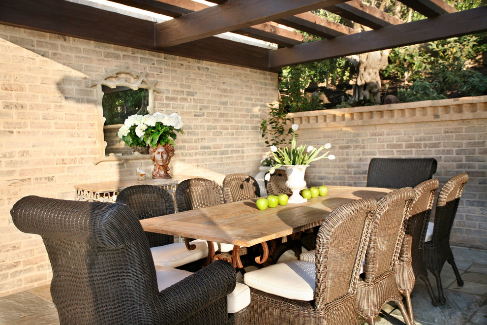 Example of a tuscan patio design in Los Angeles with a pergola
