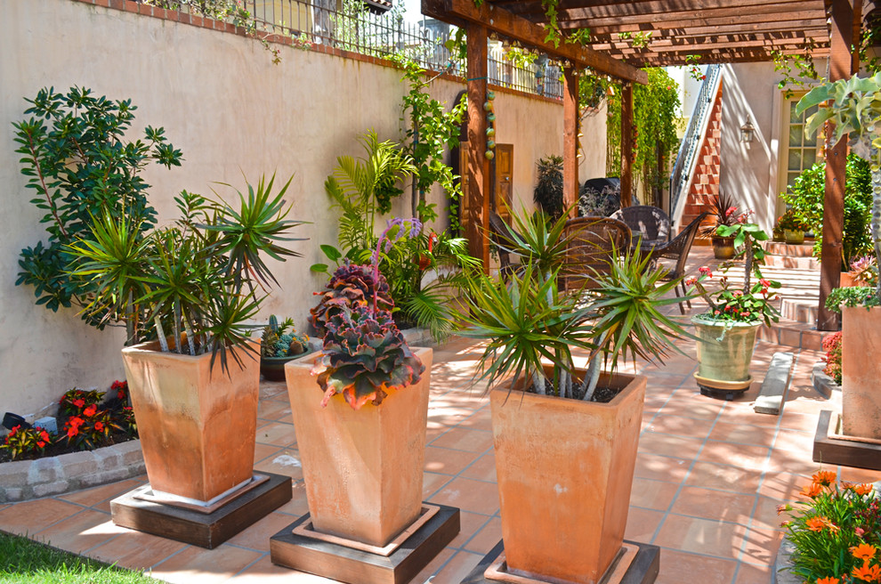 Example of a tuscan tile patio design in Los Angeles with a pergola