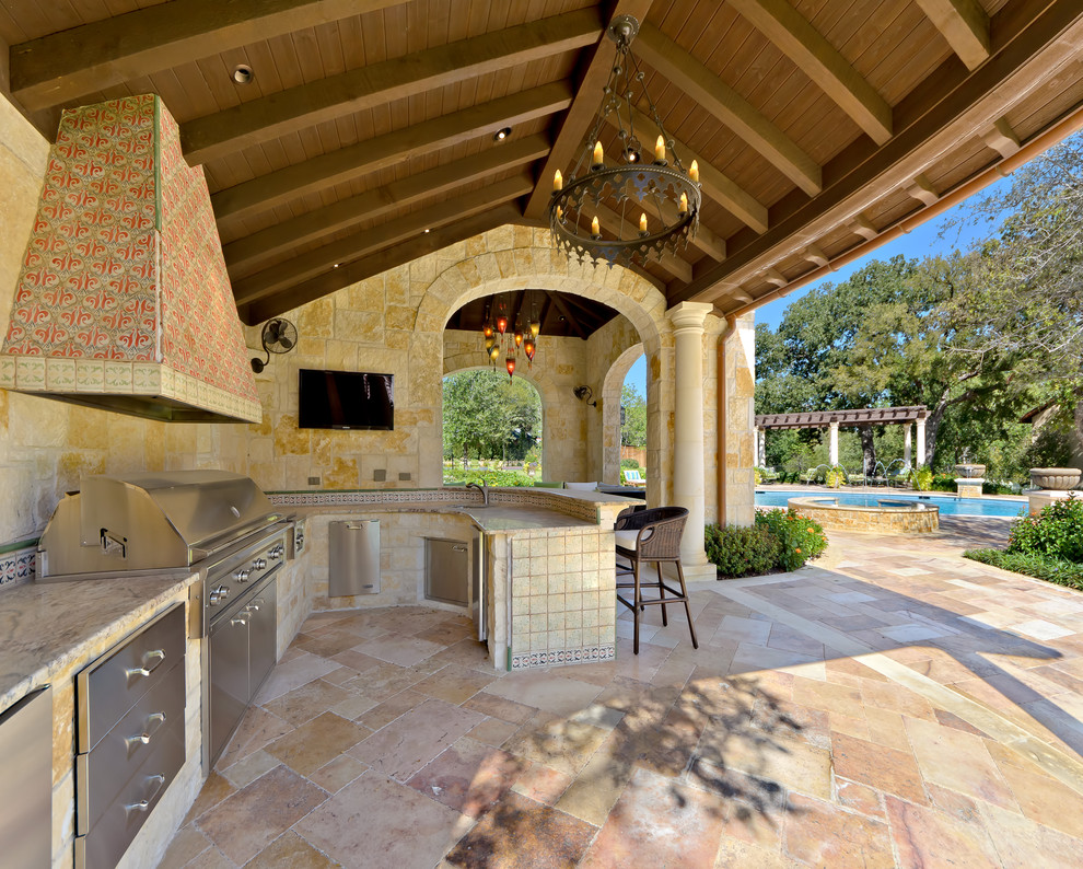 Inspiration for a mediterranean backyard patio kitchen remodel in Dallas with a pergola