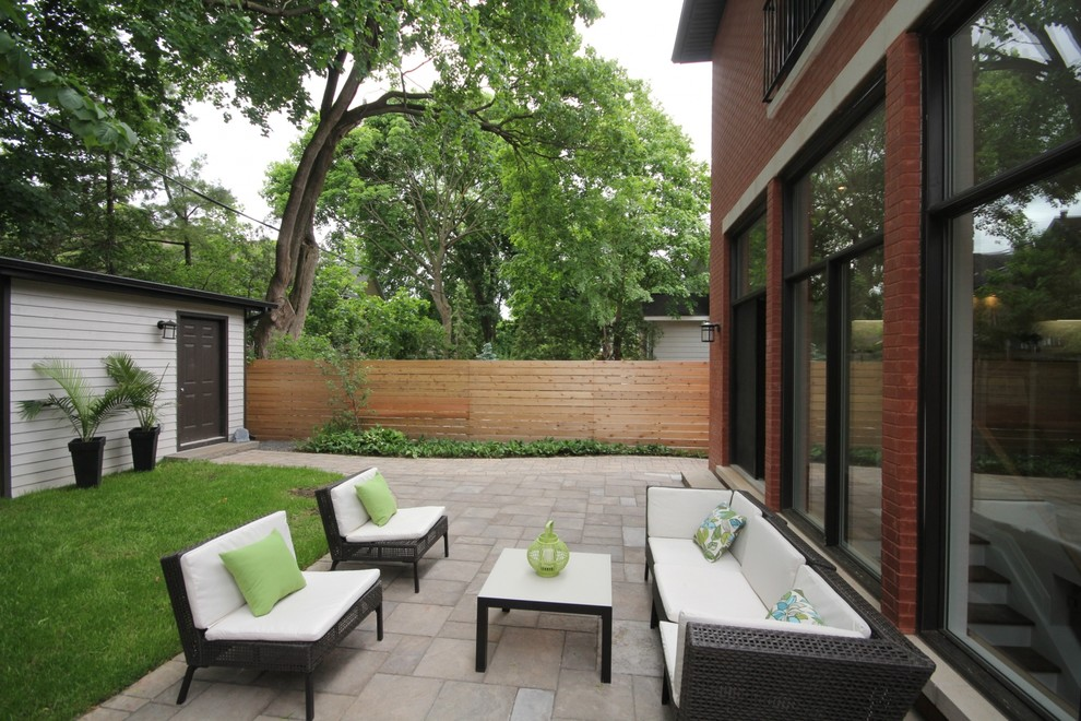 Mid-sized transitional backyard concrete paver patio photo in Ottawa with no cover