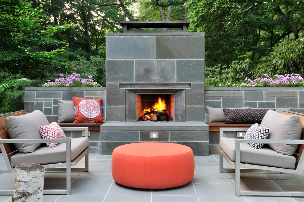 Inspiration for a mid-sized 1960s backyard stone patio remodel in Boston with a fire pit