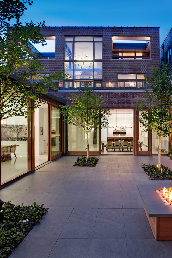 Example of an urban courtyard patio design in Chicago with a fire pit