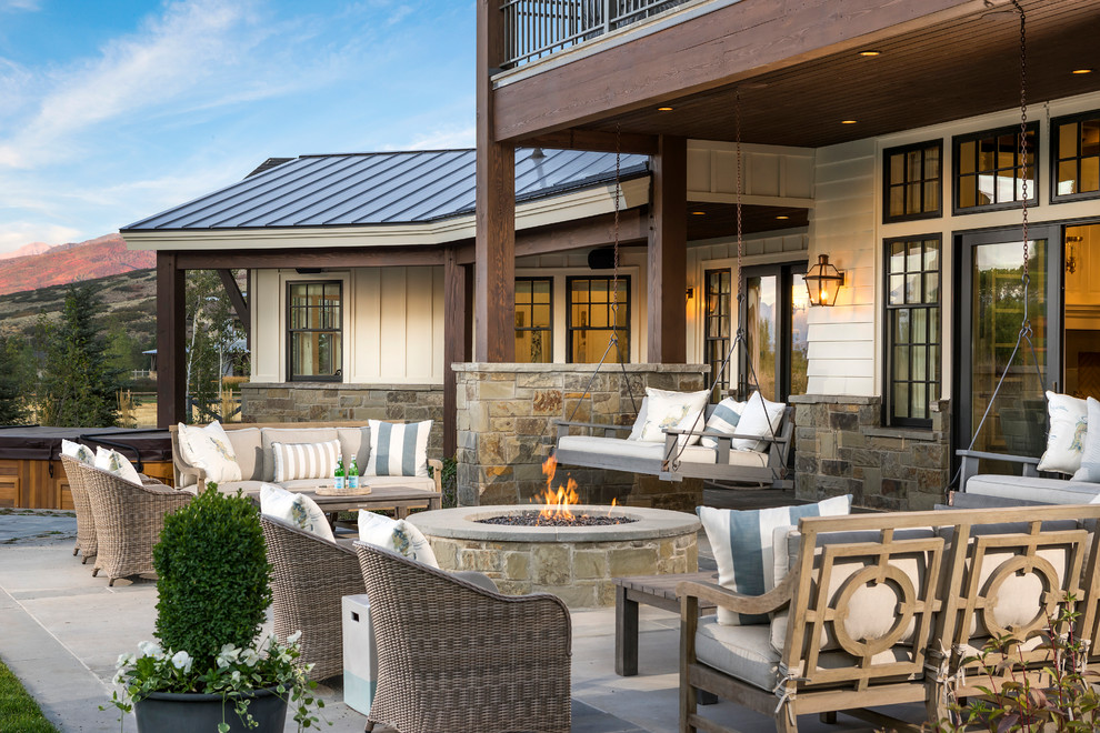 Example of a cottage patio design in Salt Lake City with a fire pit and a roof extension