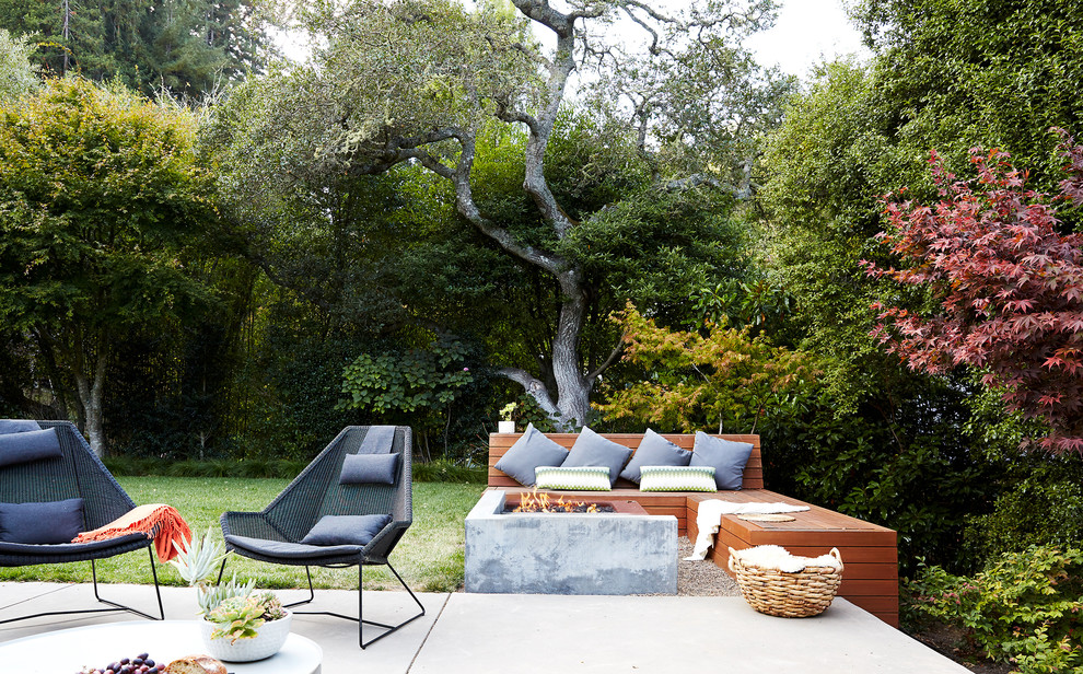 Example of a midcentury modern backyard patio design in San Francisco with a fire pit