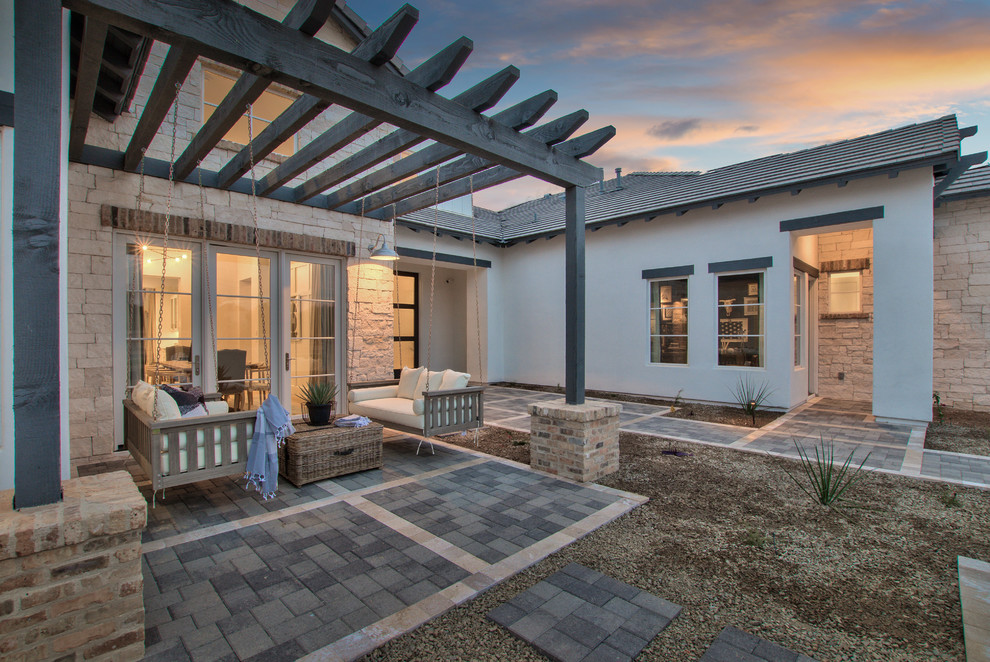 Example of a country backyard concrete paver patio design in Phoenix with a pergola
