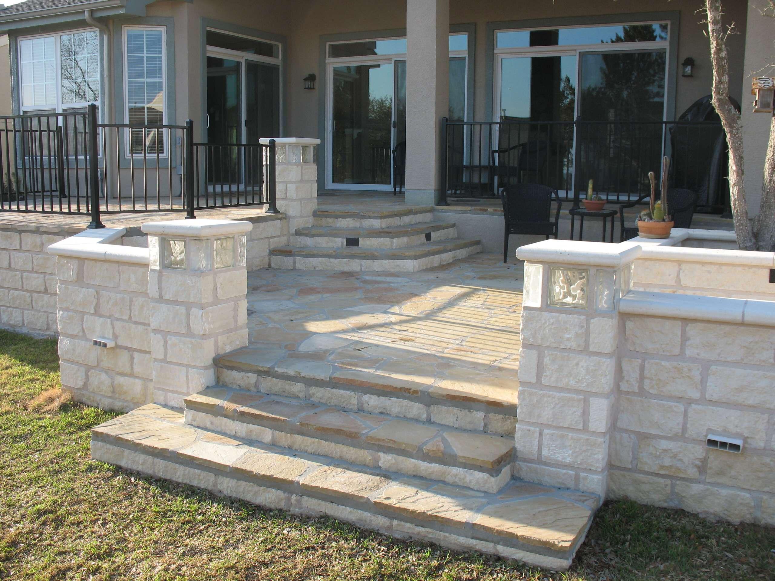 Modern flagstone patio w/ limestone walls, lighted glass block columns
