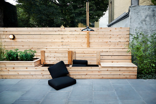 There is a multi-use feature in this yard. It is part bench, part storage, and part raised garden bed. This is a great structure that brings a number of differing elements to the yard space.