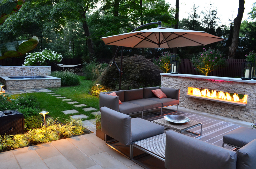 Example of a transitional backyard patio design in New York with a fireplace